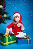 Santa girl with Cristmas gifts. Santa girl playing with Cristmas gifts near the Christmas tree Royalty Free Stock Images