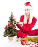 Santa  girl decorates the Christmas tree Stock Photos