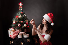 Santa girl decorates Christmas tree. Stock Photo