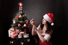 Santa girl decorates Christmas tree. stock photo