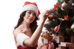 Santa girl decorates Christmas tree. royalty free stock image