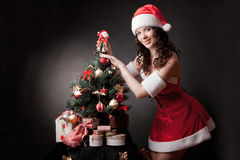 Santa girl decorates Christmas tree. stock image