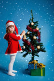 Santa girl  decorating Christmas tree Stock Images