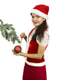 Santa girl decorating conifer branch. Pretty girl in Santa helper costume decorating conifer branch with red bauble, Christmas and New Year image, isolated on royalty free stock photography