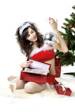 Santa girl deploying boxes with gifts Royalty Free Stock Photo