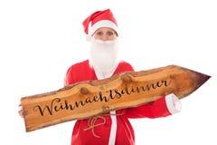 Santa Girl, die ein hölzernes Brett mit dem deutschen Wort, an lokalisiert hält Stockfotos