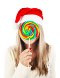 Santa girl eating lollipop Stock Photo