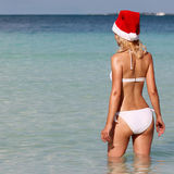 Santa Girl en la playa tropical. Mujer joven rubia hermosa imagen de archivo libre de regalías