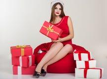 Santa Girl está sentando-se com o presente vermelho do Natal fotos de stock royalty free