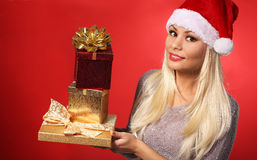 Santa Girl with Gift Boxes over red background. Christmas Stock Images