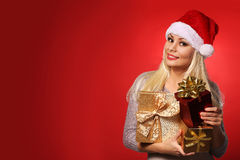 Santa Girl with Gift Boxes over red background. Christmas Stock Image