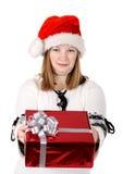 Santa girl giving a gift. Girl in a santa hat gives a gift Stock Photos