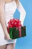 Santa girl hiding a present Stock Image