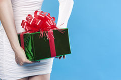Santa girl hiding a present gifts Stock Photo