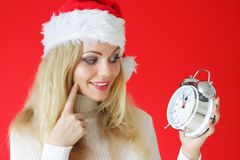 Santa girl holding alarm clock Royalty Free Stock Images