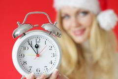 Santa girl holding alarm clock Royalty Free Stock Photography