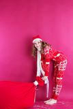 Santa girl is holding big red christmas bag Royalty Free Stock Image