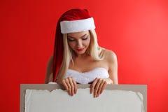 Santa girl holding blank billboard. Santa girl holding blank vintage sign billboard. Christmas woman in Santa hat showing paper sign Royalty Free Stock Photos