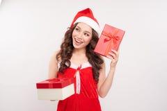 Santa girl holding christmas gift. Young happy woman in santa ha royalty free stock image