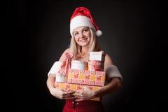 Santa girl is holding Christmas gifts. stock photo