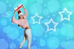Santa girl holding gift above head on blue starry Royalty Free Stock Photos