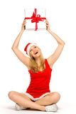 Santa girl holding gift above her head Royalty Free Stock Images