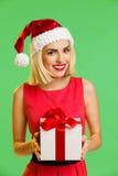 Santa girl holding a gift Stock Photos