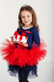 Santa girl is holding gift box, christmas time Stock Photo