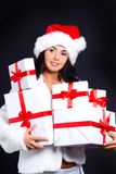 Santa girl holding a lot of gifts. Royalty Free Stock Image