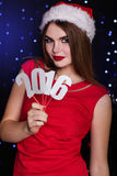 Santa girl is holding paper digits 2016. Pretty girl is wearing red fashion dress and santa hat is holding silver paper digits 2016. Smiling beautiful woman royalty free stock photos