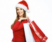 Santa girl holding shopping bag. christmass portrait of young w. Oman with red santa hat. white background isolated Stock Image