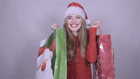 Santa girl holding shopping bags, enjoying snowfall in studio.