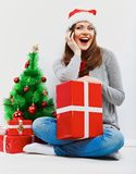 Santa girl isolated portrait with christmas gift, cristmas tree Royalty Free Stock Photos