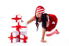 Santa girl its hands on a gifts. Santa girl is sitting on its hands on a pile of gifts. Holidays Stock Photo