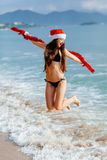 Santa girl jumping in the sea on the beach Stock Image