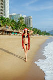 Santa girl making wish on the beach in tropics Stock Images