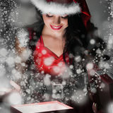 Santa girl opening the magical present Royalty Free Stock Photography
