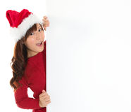 Santa girl peeking from behind blank sign billboard. Advertising photo of young surprised Christmas woman in Santa hat showing paper sign. Asian female model Stock Photography