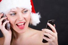 Santa girl with phone. The christmas girl with phone Stock Photo