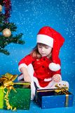 Santa girl playing with Cristmas gifts Stock Photo