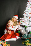 Santa girl playing with little girl. Near the Christmas tree royalty free stock photos