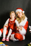 Santa girl playing with little girl. Near the Christmas tree stock photo