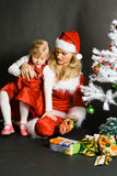 Santa girl playing with little girl. Near the Christmas tree stock image