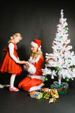Santa girl playing with little girl. Near the Christmas tree stock images