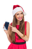 Santa girl pointing at mobile phone Stock Images