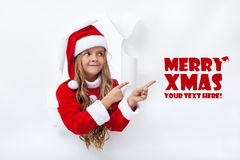 Santa girl pointing to copy space. Leaning through hole in paper Royalty Free Stock Photos