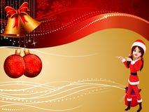 Santa girl pointing towards two big jingle bell Stock Photography