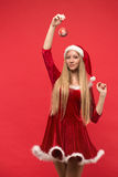 Santa girl posing on a red background with the toy. Royalty Free Stock Images