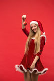 Santa girl posing on a red background with the toy. Royalty Free Stock Photography