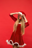 Santa girl posing on a red background with the toy. Stock Photography